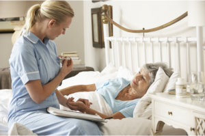 caregiver taking care of an old lady in bed